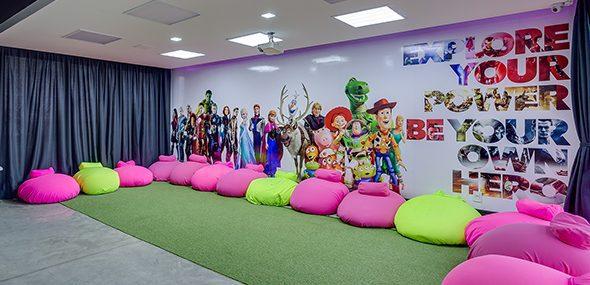 Sala de aula com puffs e chão de grama sintética, em sua parede tem personagens da Disney, Marvel e Pixar.