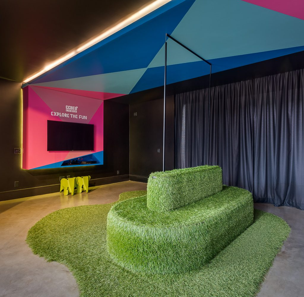 Sala com dois televisores em cada lado e no meio há uma poltrona arredonda coberta de grama sintética