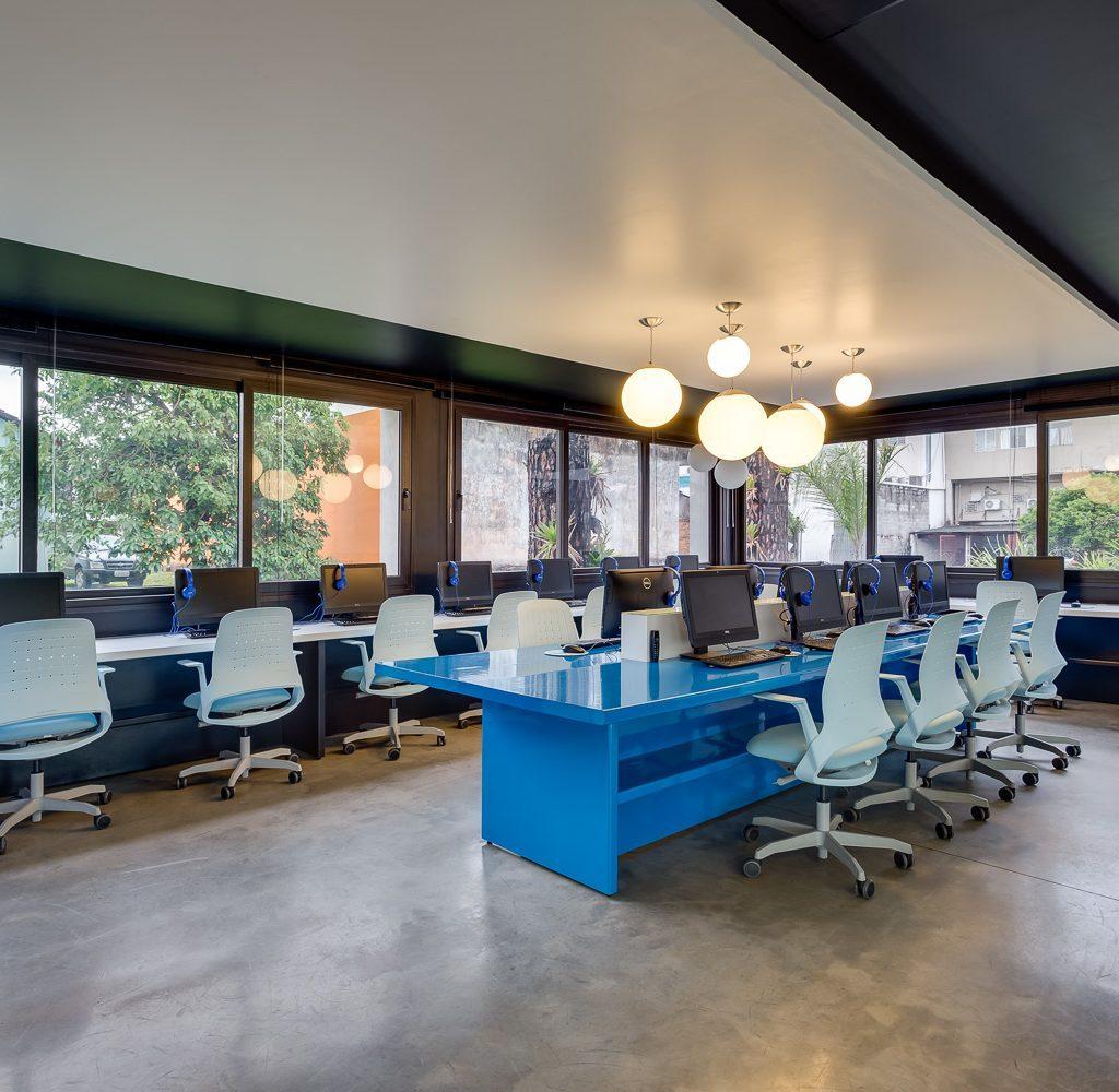 Sala com computadores e mesas azuis, em sua volta tem cadeiras.
