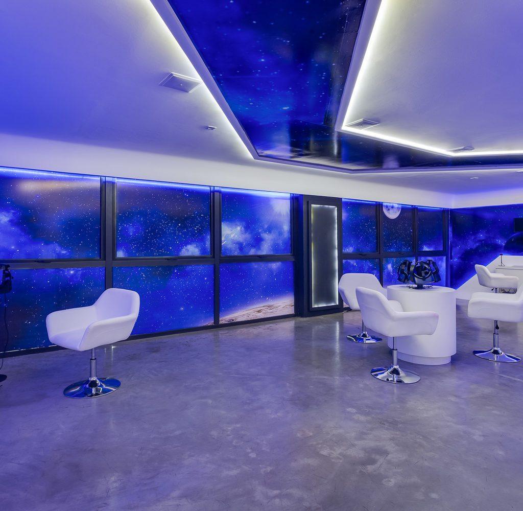 Sala com poltronas brancas, luzes azuis e óculos de realidade virtual.