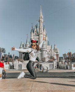 Mulher pulando em frente a um castelo na Disney.
