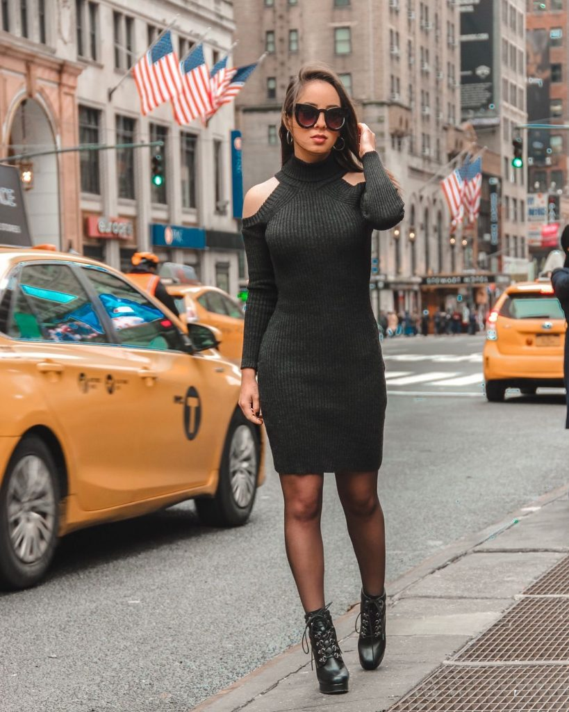 Na foto Jessica está em uma rua em Nova York, ao fundo passam táxis amarelos e há prédios com a bandeira dos Estados Unidos