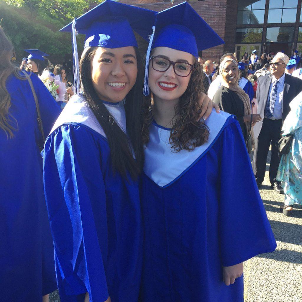 Duas alunas formadas com beca e capelo azul, elas estão sorrindo
