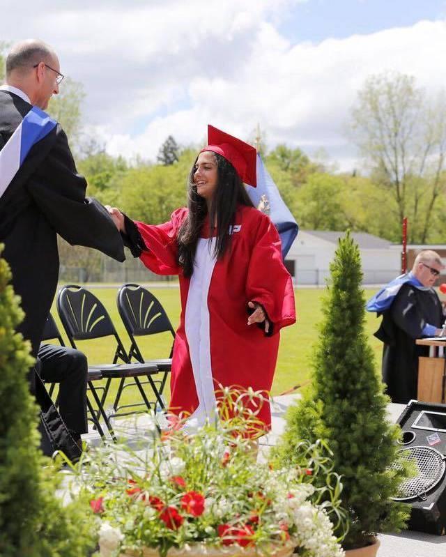 Luana está se formando em uma escola nos Estados Unidos, na foto ela está vestida com uma beca vermelha e capelo vermelho