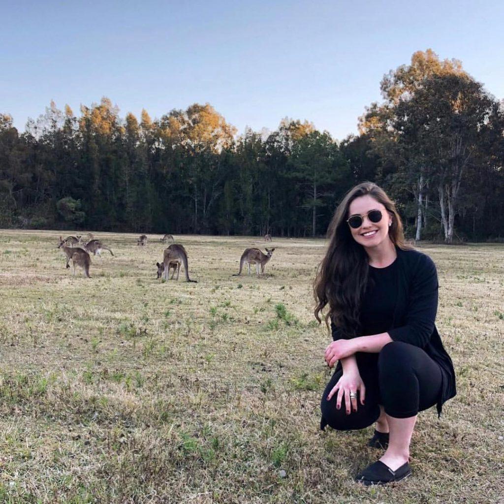 Mulher agachada vestida de preto em um gramado de outono, ao fundo tem cangurus australianos.