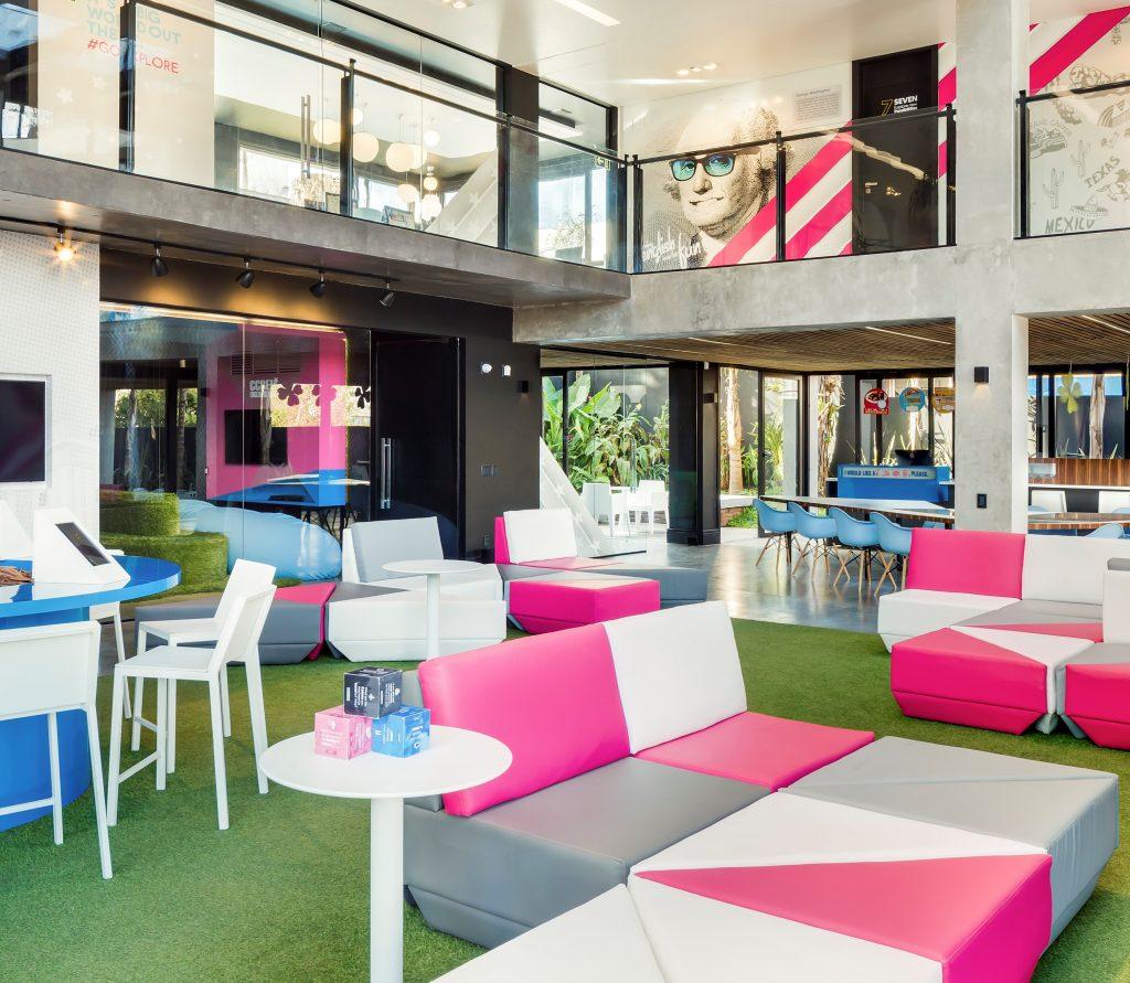 Espaço com sofás rosa e branco em formato triangular.